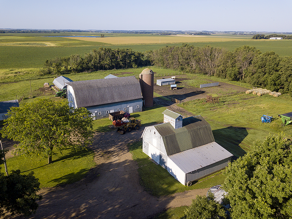 Aerial view of property released farm buildings in South Dakota with fields in the background.