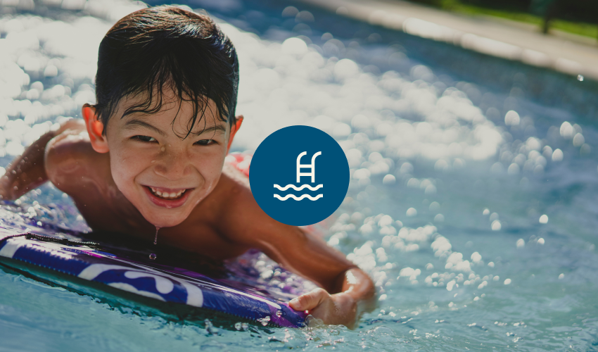 Photograph of a young boy in a pool, smiling and floating on a foam kickboard.
